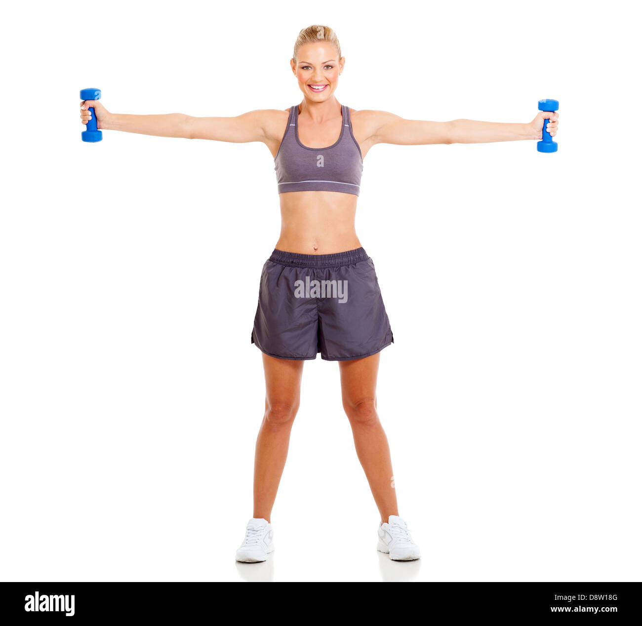 portrait of fit woman working out with dumbbells - Stock Image
