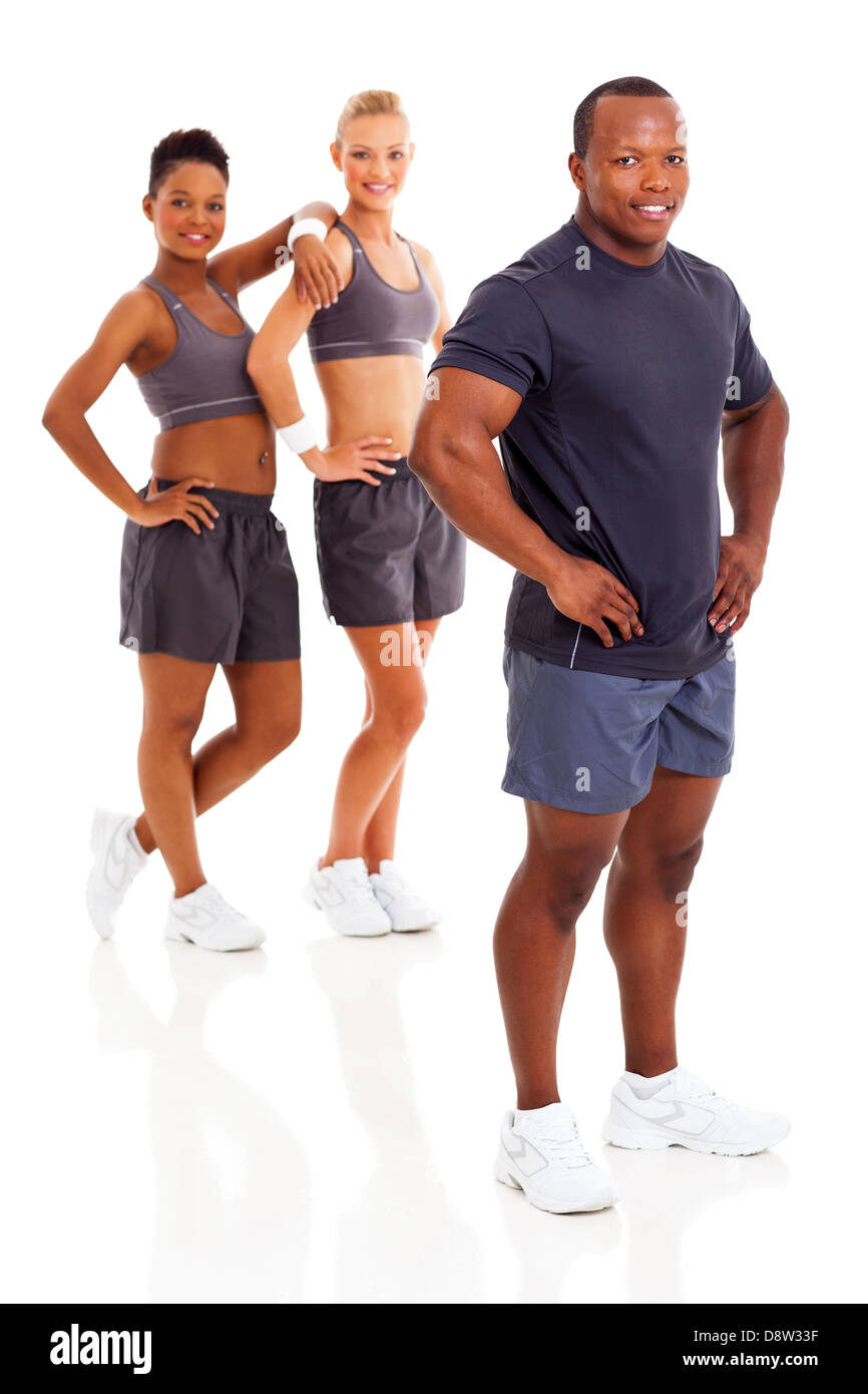 portrait of fit african man instructor posing with two gym members on background - Stock Image