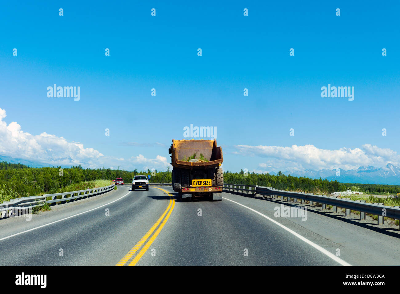 Construction vehicle, oversize, wide load, traveling south on Highway 3, north of Anchorage, Alaska, USA - Stock Image