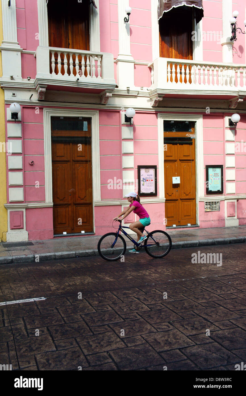 Young woman bicyclist riding by a pink Spanish colonial building on Calle Sesenta, Merida, Yucatan, Mexico - Stock Image