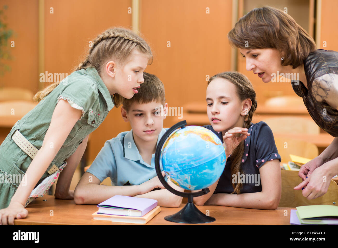 pupils studying a globe together with teacher - Stock Image