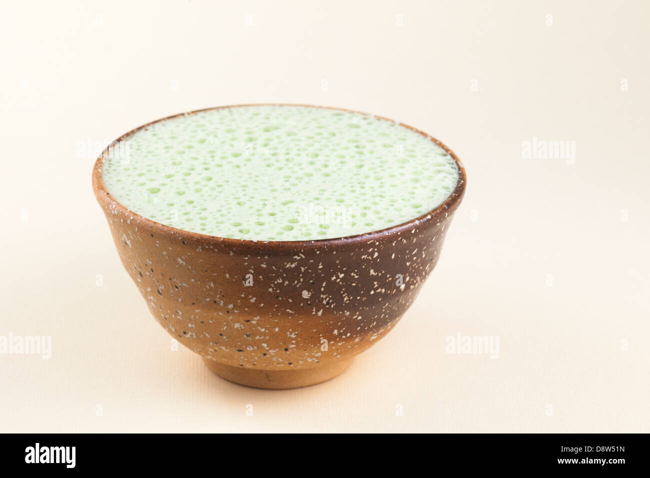 Matcha latte made with almond milk served in matcha bowl - Stock Image