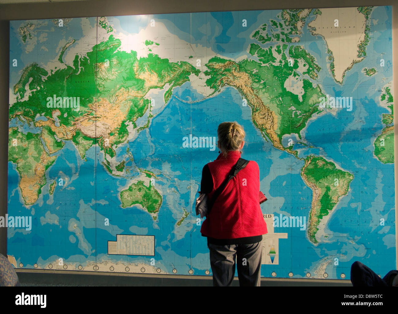 A woman in a red jacket, back view, looking at a large map of the world on a wall at Auckland Airport - Stock Image
