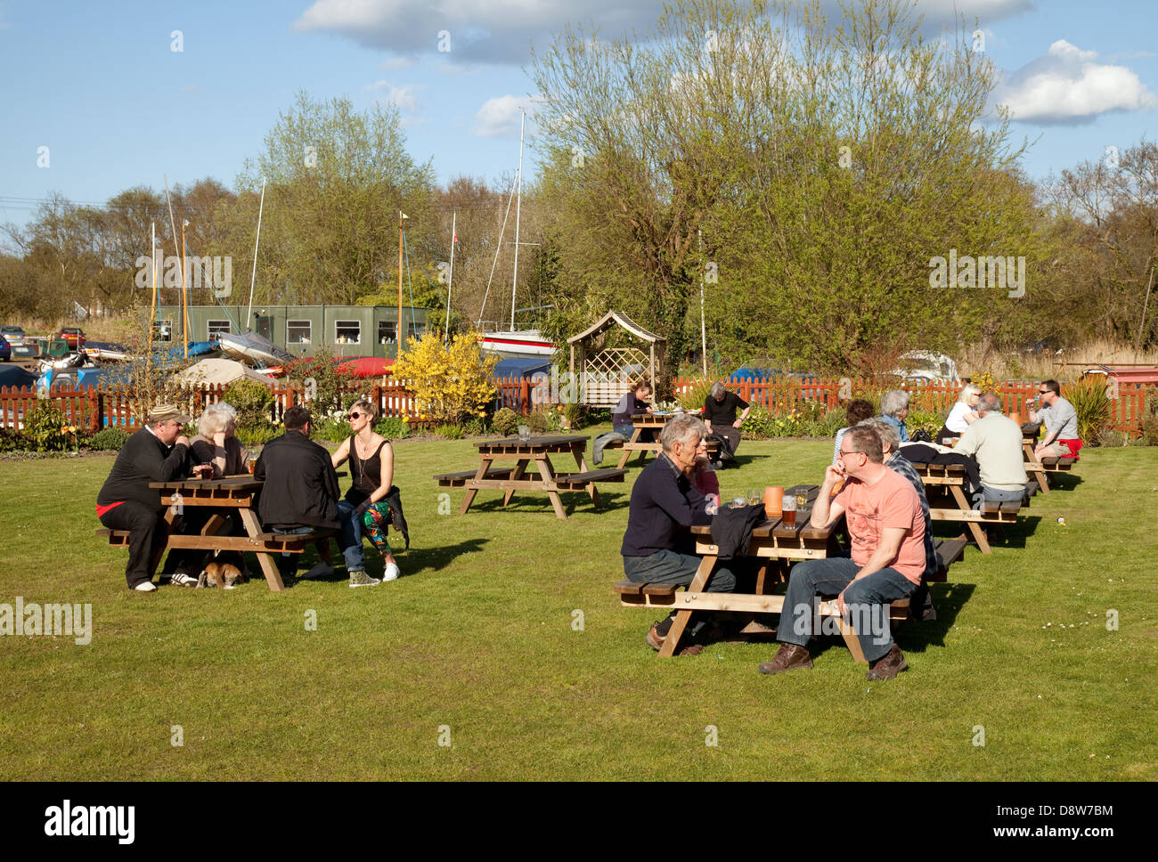 People sitting outside drinking in the beer garden, The Pleasure Boat Inn, Hickling, Norfolk UK - Stock Image
