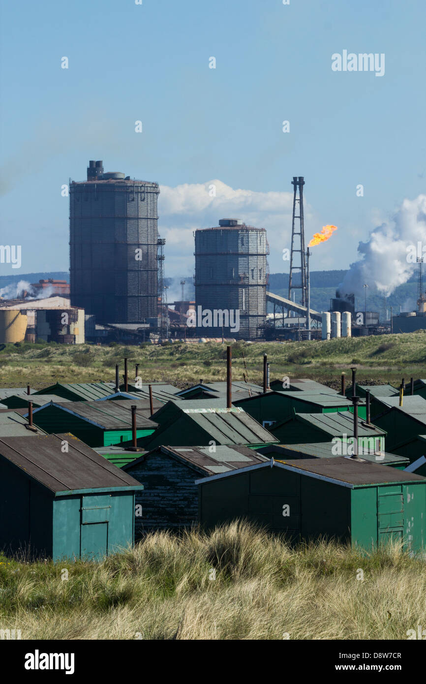 View over Fishermens Huts with Redcar Steelworks blast furnace in background. South Gare, Redcar, England, UK - Stock Image