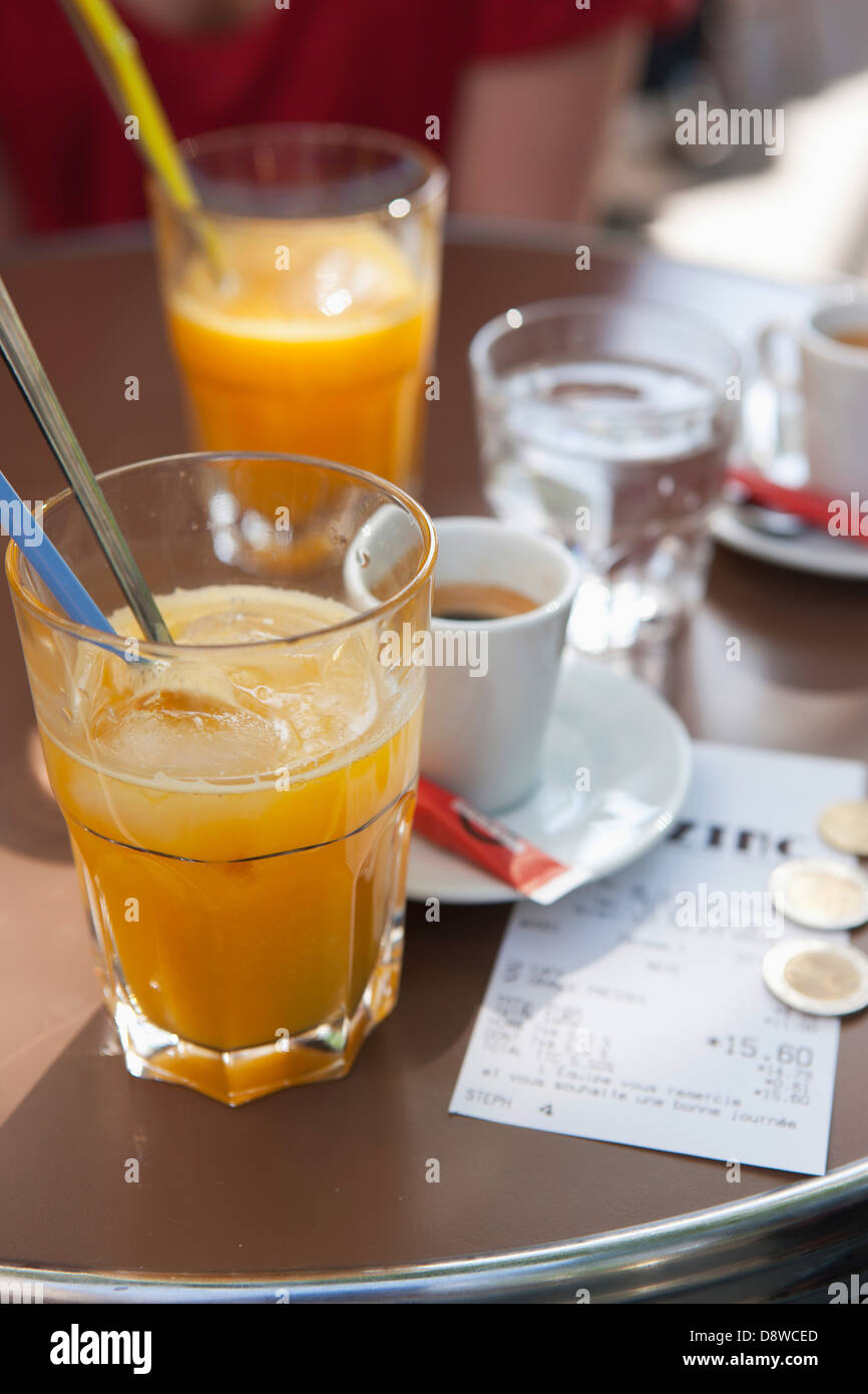 Orange juice,expresso and the bill on a table in a Bistrot - Stock Image
