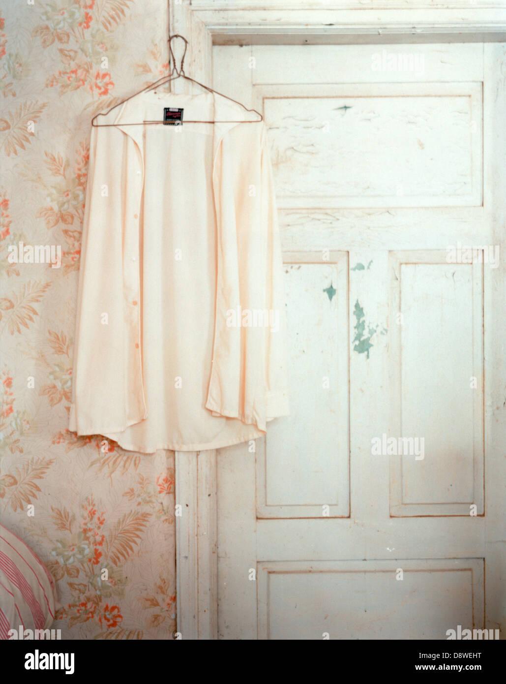 Shirt on hanger hung on doorframe - Stock Image