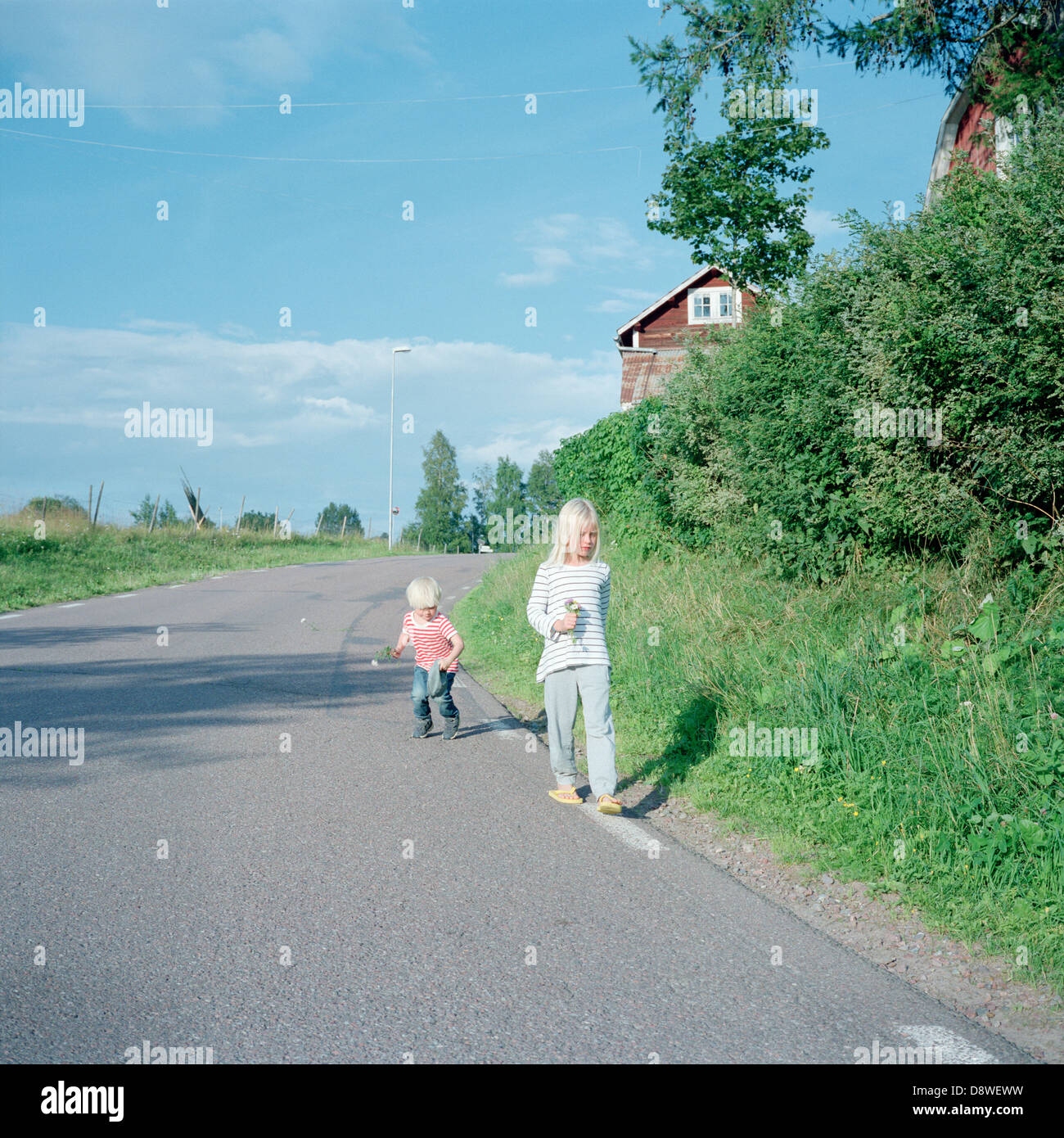 Boy and girl walking down country road - Stock Image