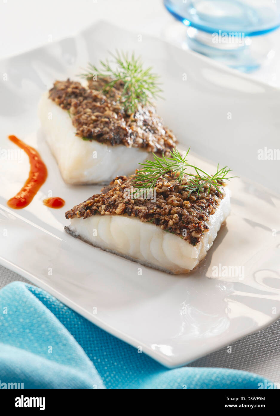 Thick pieces of cod with black olive and pine nut crust - Stock Image
