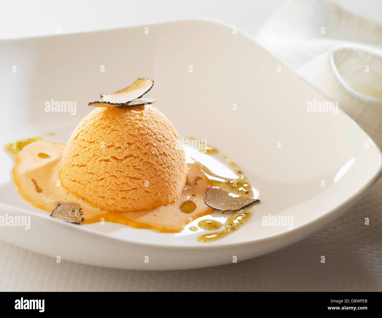 Red pepper savoury ice cream with thinly sliced truffles - Stock Image