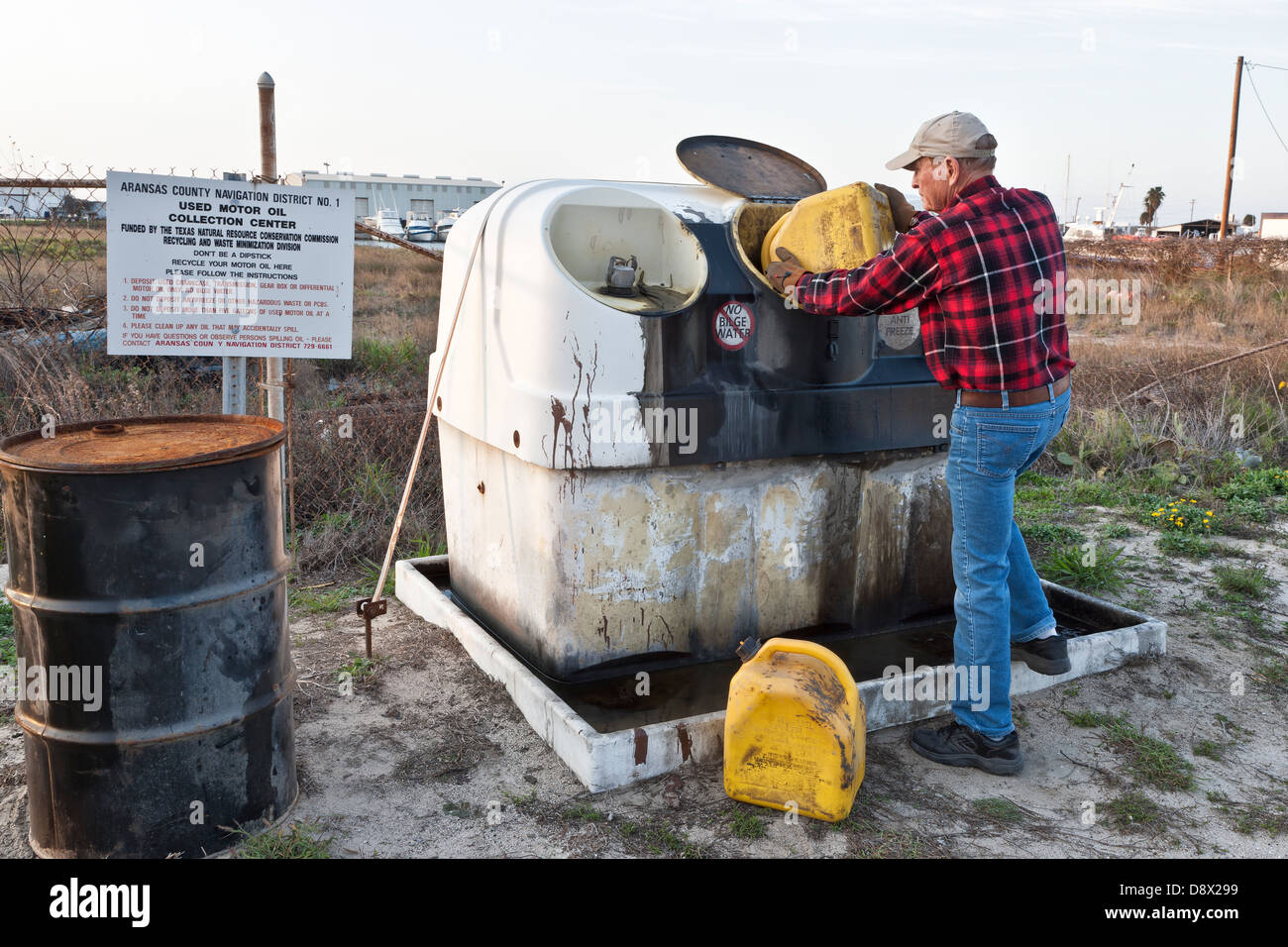 Boat owner recycling used motor oil. - Stock Image