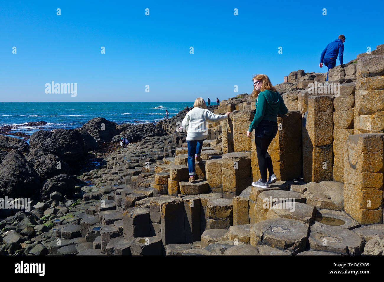 Tourists on Giants causeway - Stock Image