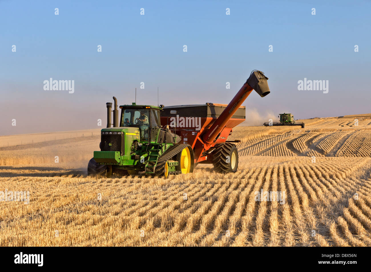 John Deere Tractor pulling Brent Bank Out Wagon, wheat harvest. - Stock Image
