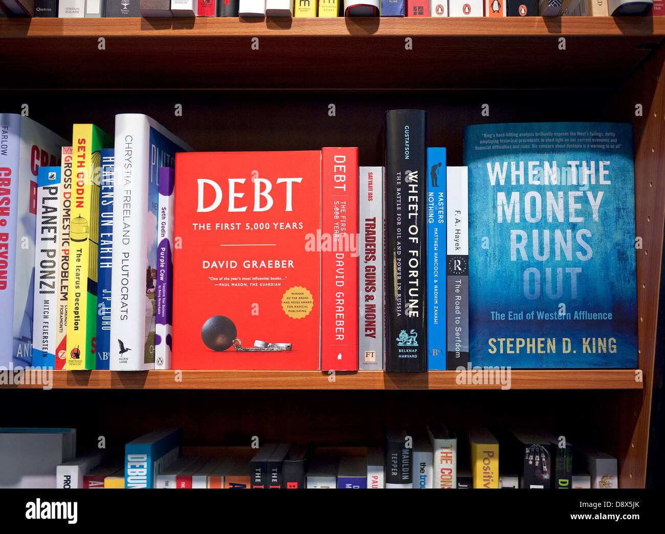 money and debt books on shelf in book shop - Stock Image