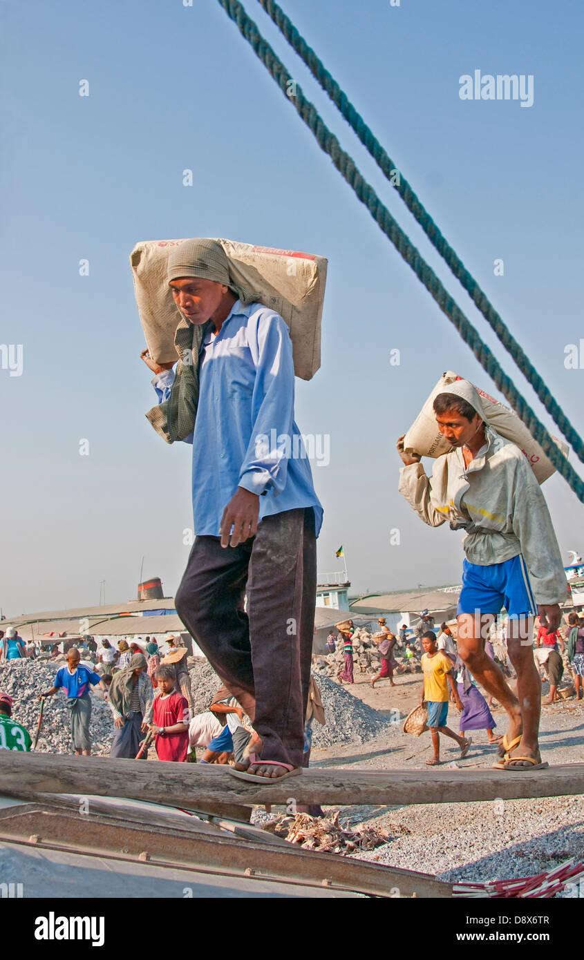 Laborers unloading barge on Ayeyarwaddy River near Mandalay. - Stock Image