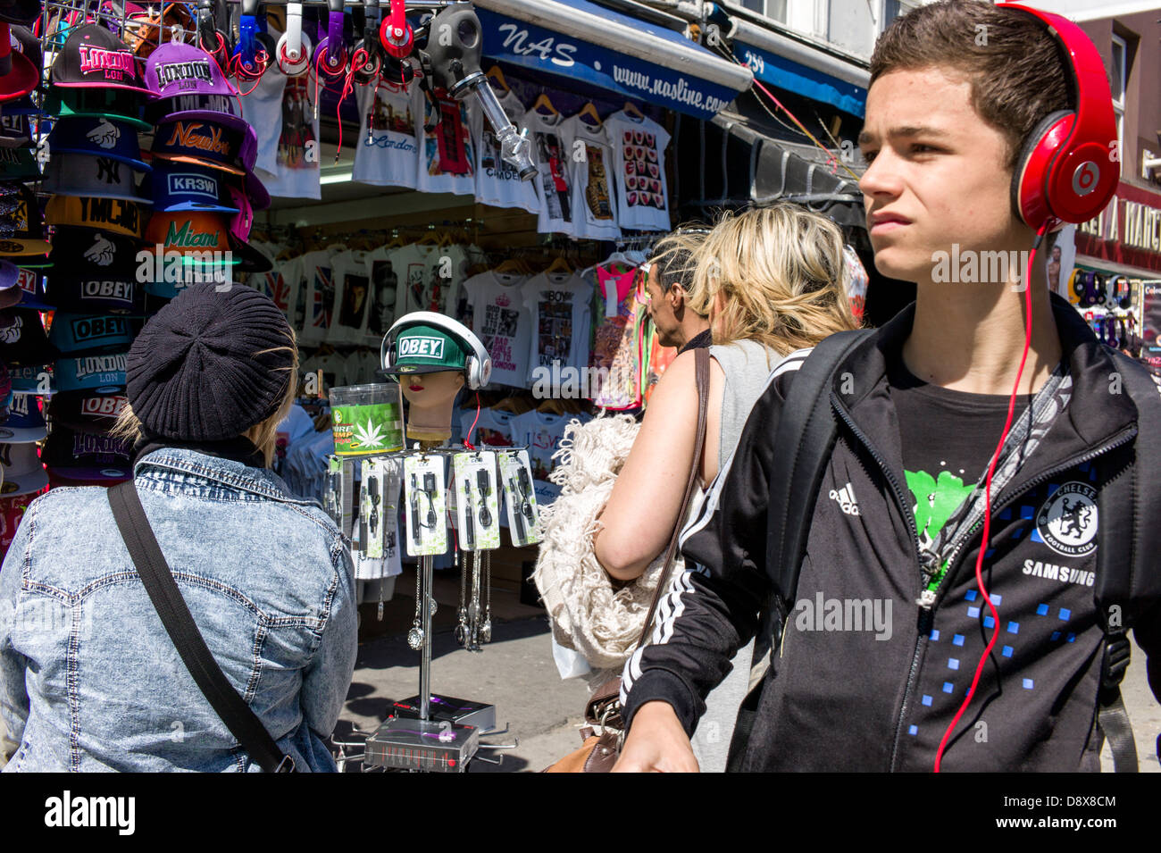 London UK, Camden Town, Camden Market, young boy, man, wearing headphones, and tourist, shoppers, looking at a market - Stock Image