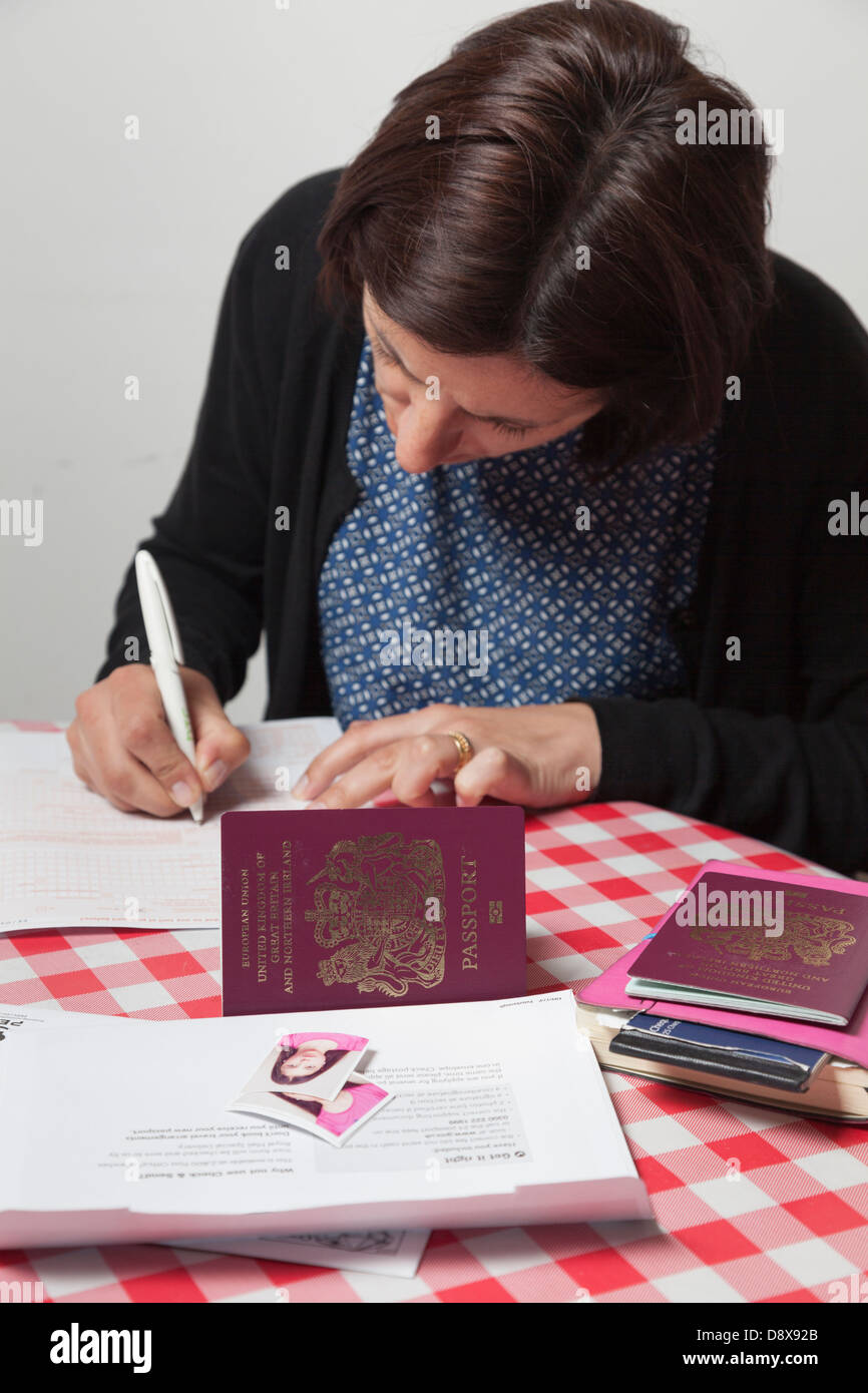 Woman filling out a passport renewal application - Stock Image