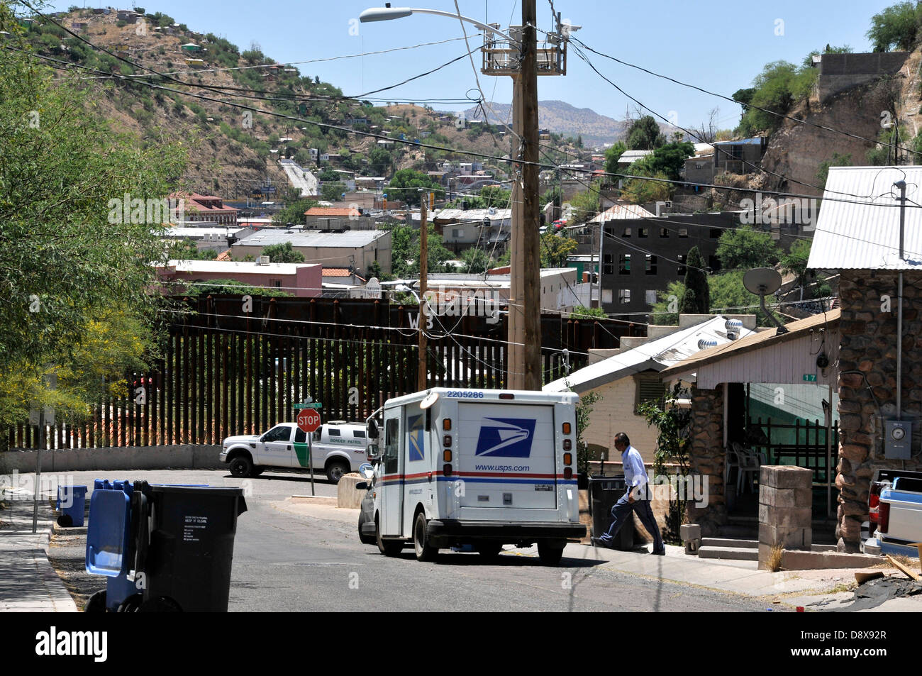 A US postal worker delivers mail to a residence near the border wall in Nogales, Arizona, USA, across from Sonora, - Stock Image