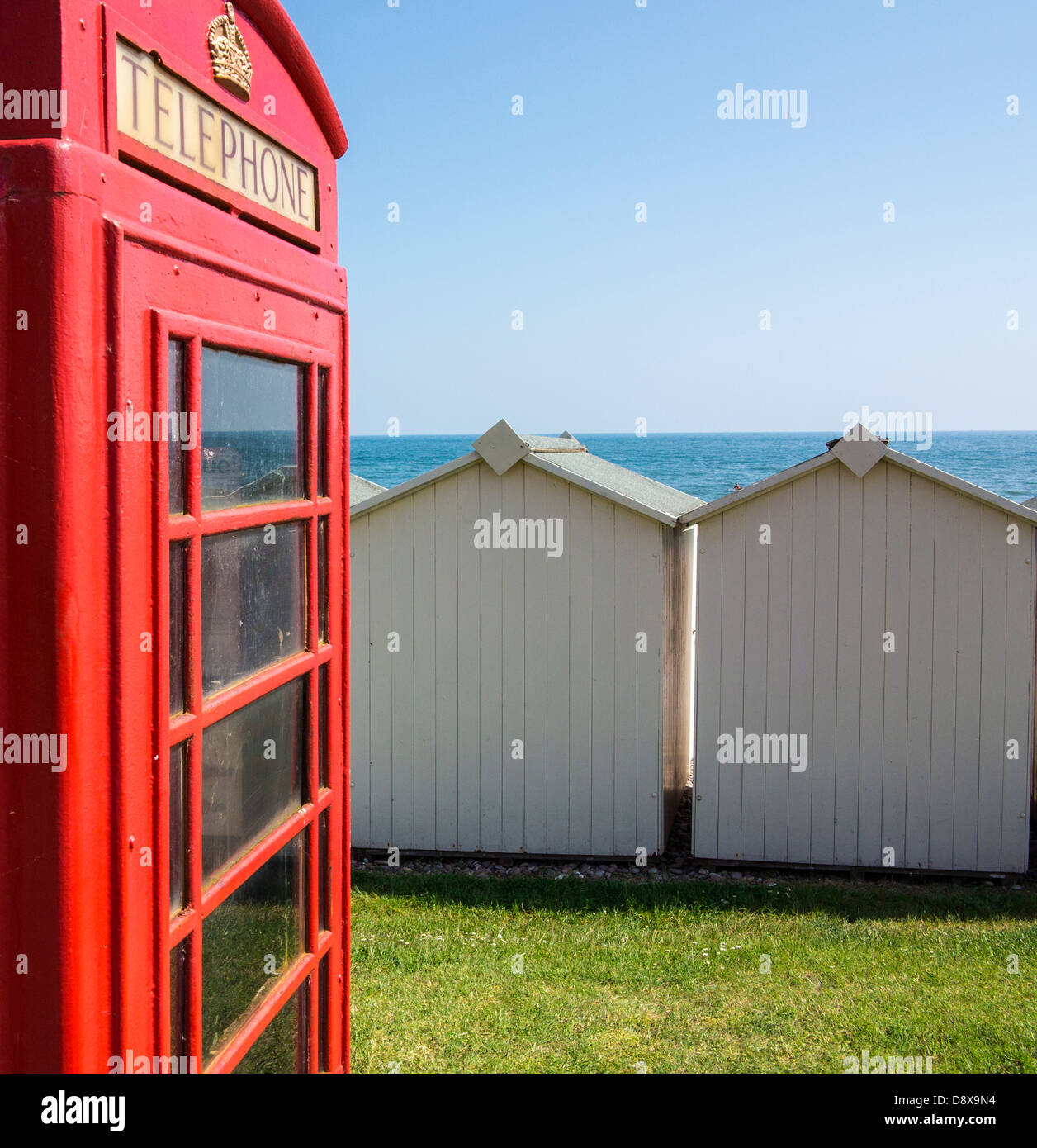Old red telephone box and beach huts on the seafront at Budleigh Salterton, Devon, England - Stock Image