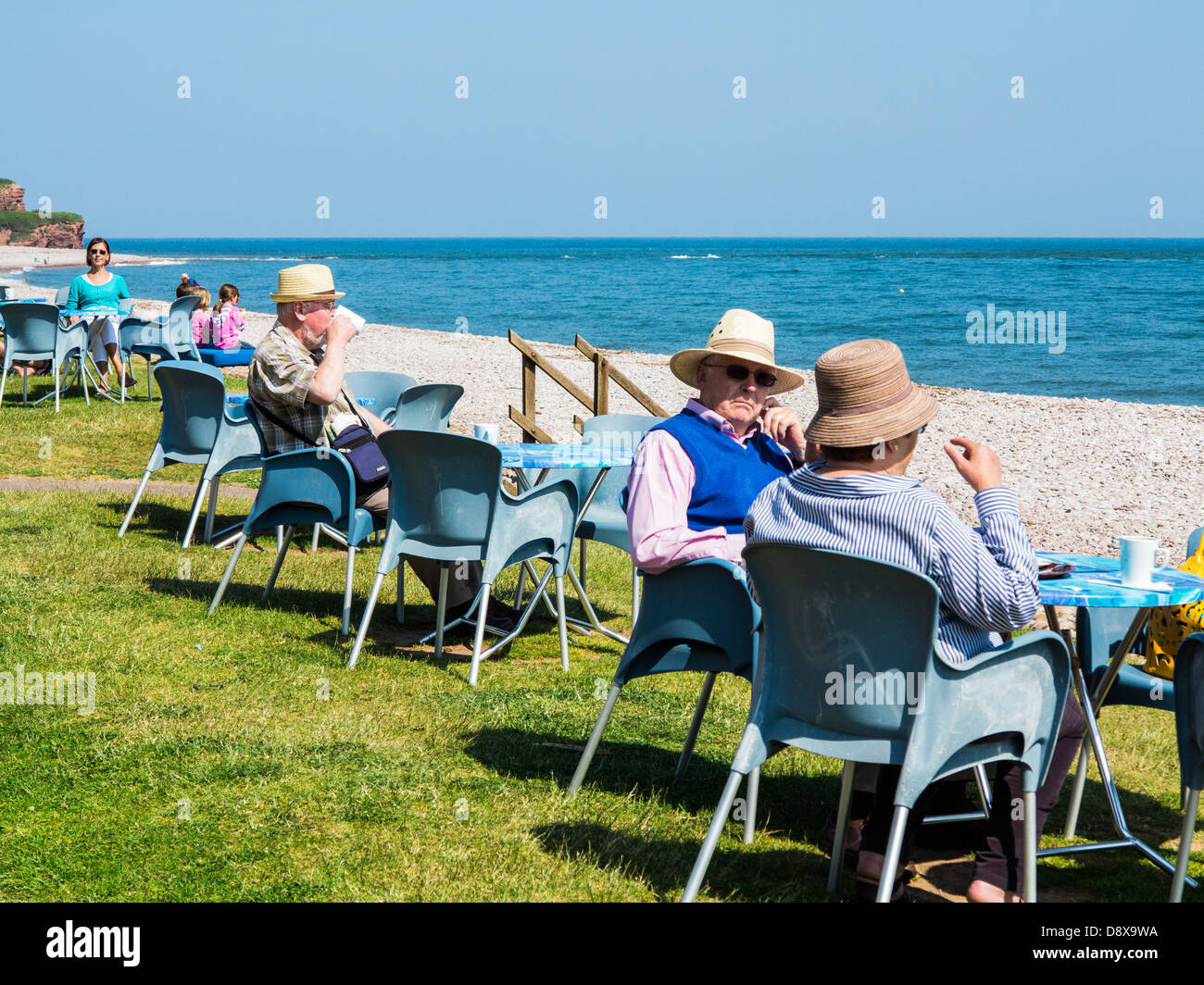 People eating and drinking alfresco at the Longboat Cafe on the seafront at Budleigh Salterton, Devon, England - Stock Image