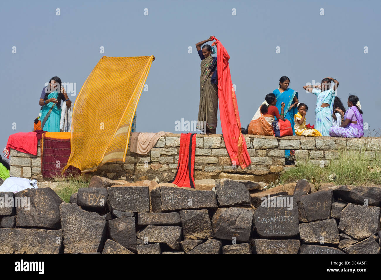 Tungabhadra river,Hampi,Karnataka,India,woman are drying their saris after a ritual bath - Stock Image