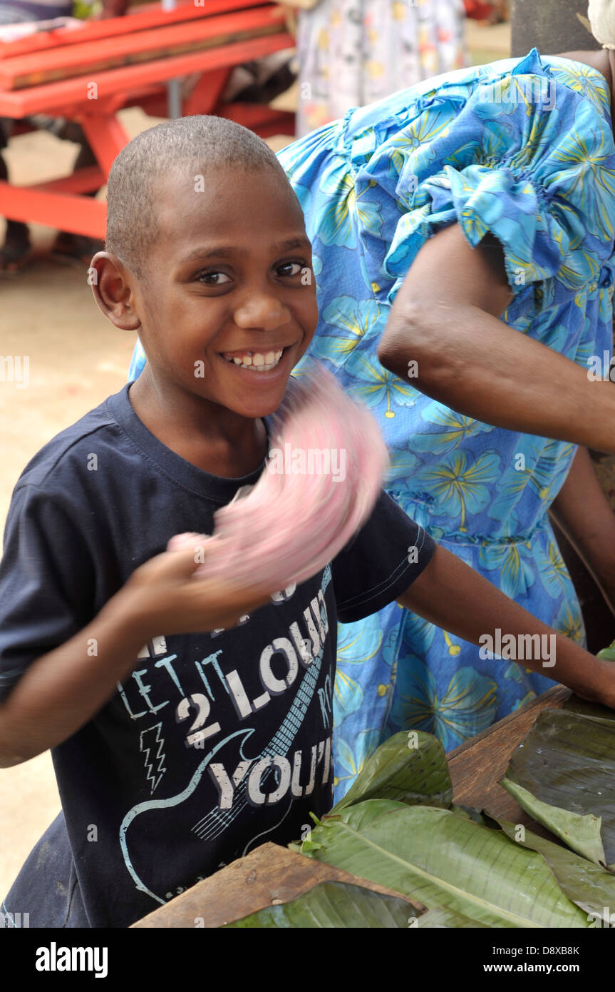 Boy scares flies away with piece of cloth at food market in Efate, Vanuatu - Stock Image