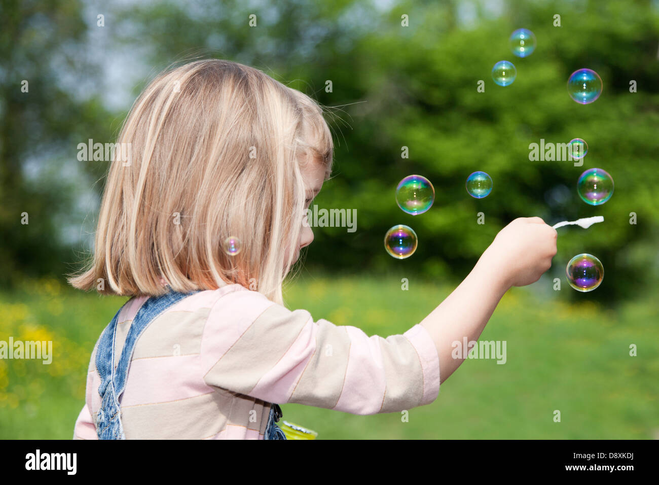 Four year-old girl balancing a soap bubbles - Stock Image