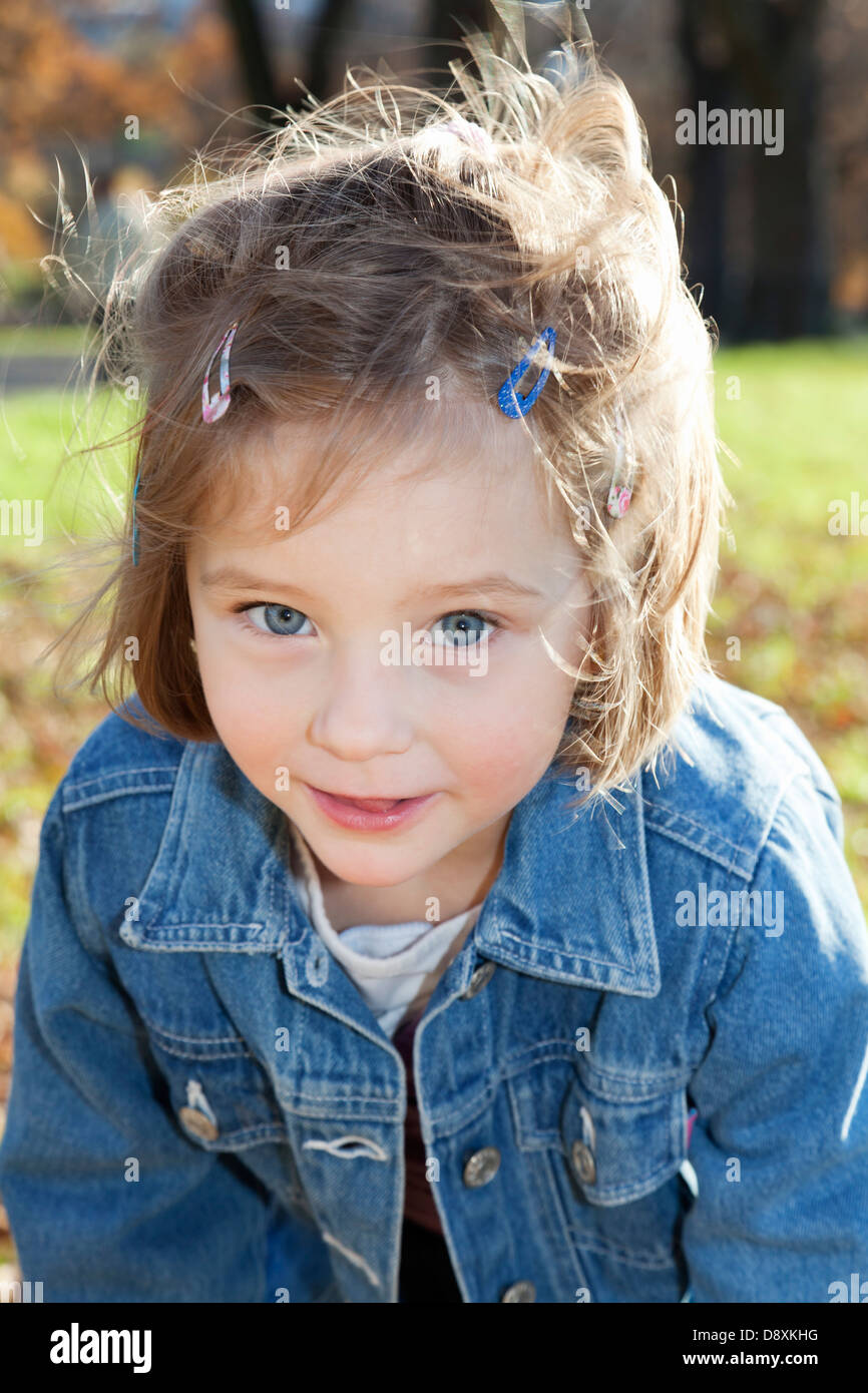 Portrait of a four year-old girl playing in a park in autumn - Stock Image