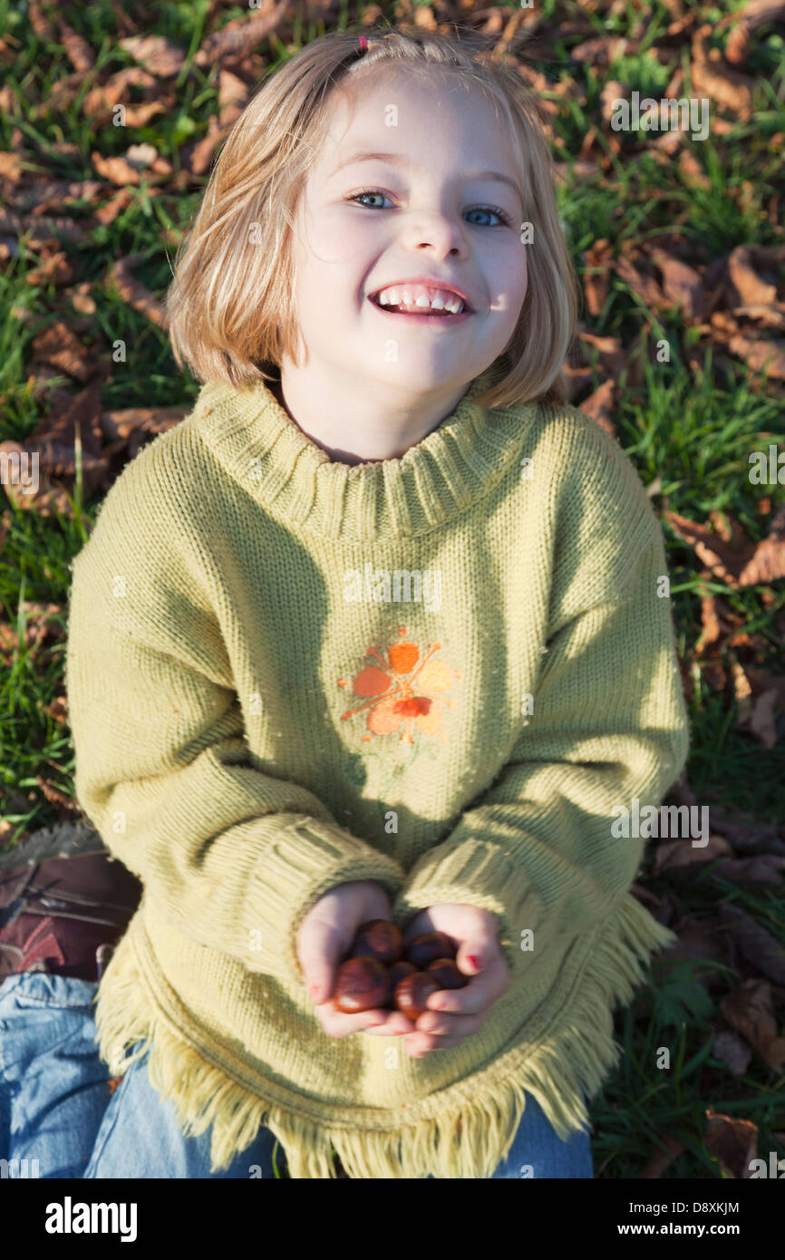 Six year old girl with chestnuts in her hands - Stock Image