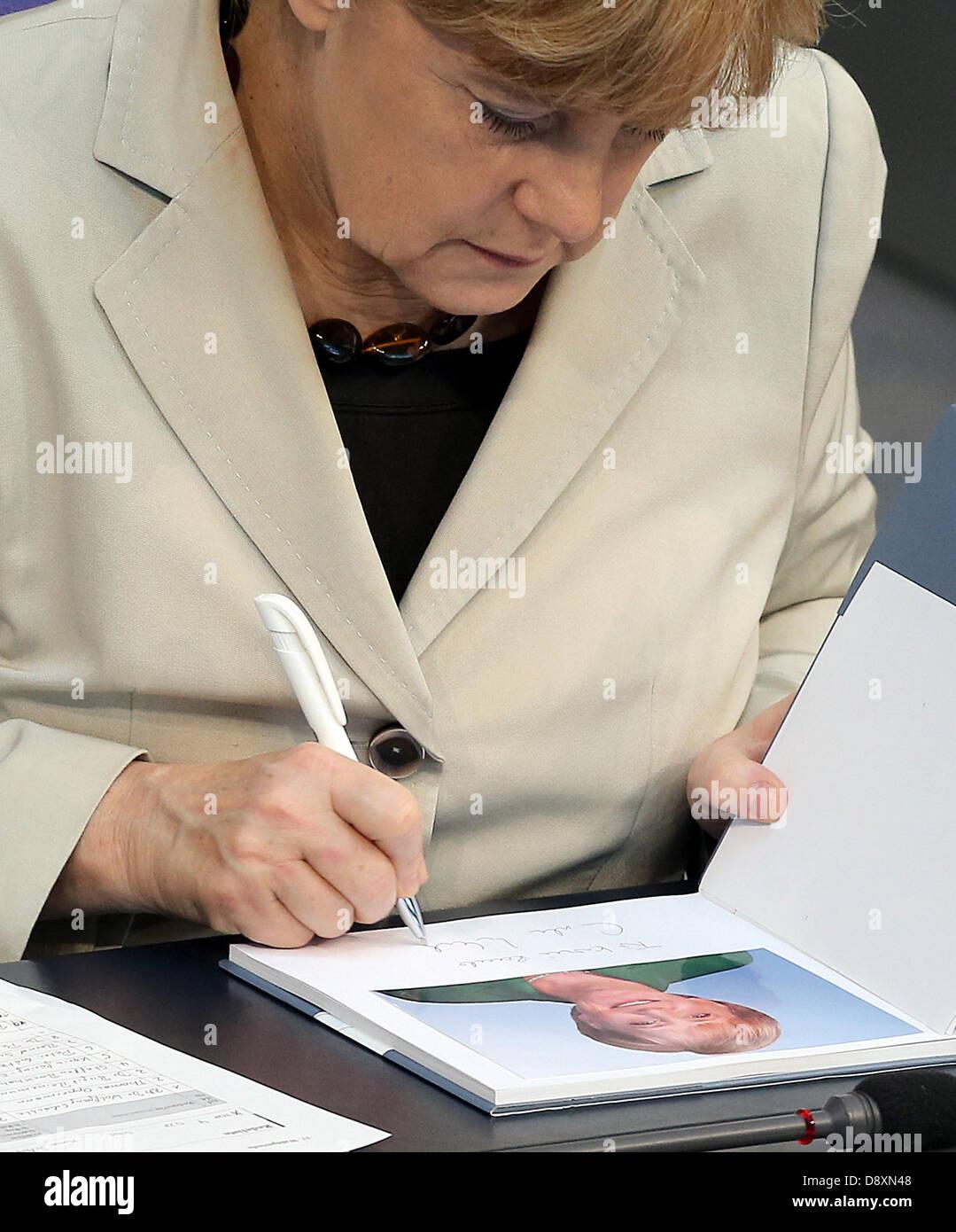 Berlin, Germany. 6th June 2013. Chancellor Angela Merkel (CDU) signs a book in the German Bundestag in Berlin, Germany, - Stock Image