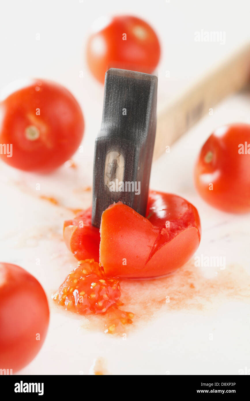 Squashing tomatoes with a hammer - Stock Image