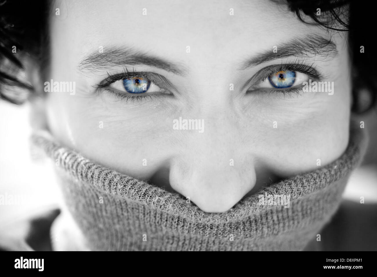 Portrait of a young shy woman with blue eyes smiling - Stock Image