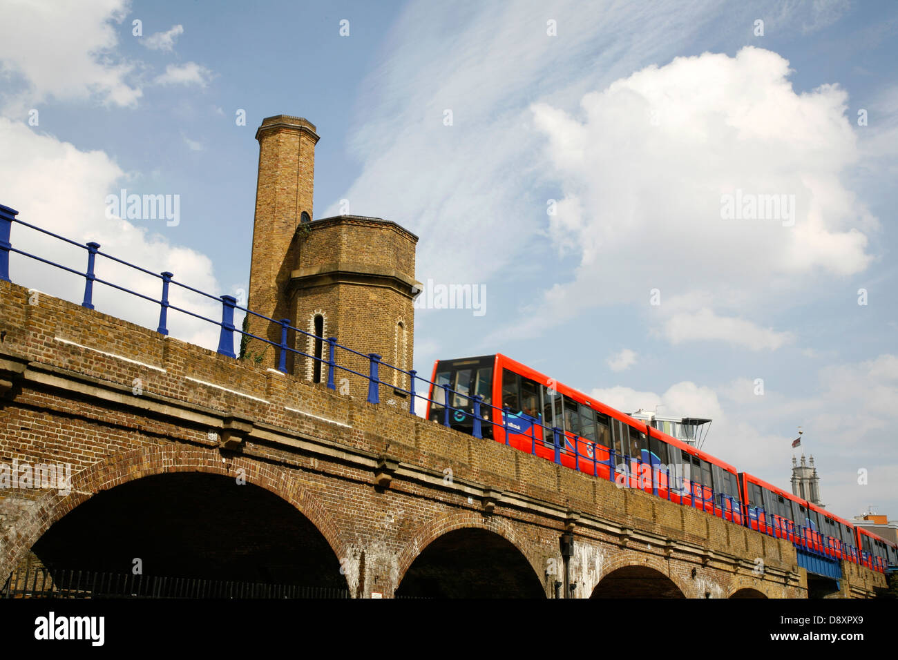 DLR train passing Limehouse Accumulator Tower, Limehouse, London, UK - Stock Image