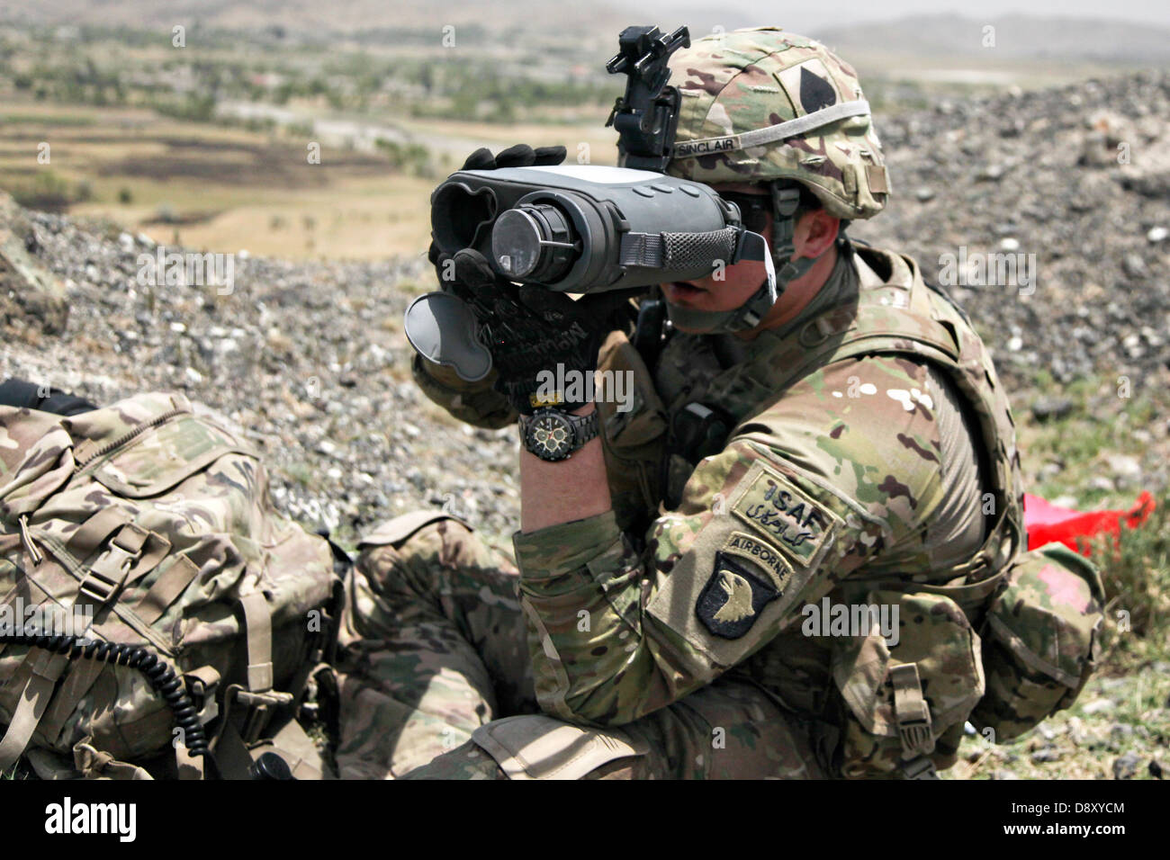 A US Army sergeant with the 101st Airborne Division scans the area with a lightweight laser designator rangefinder - Stock Image