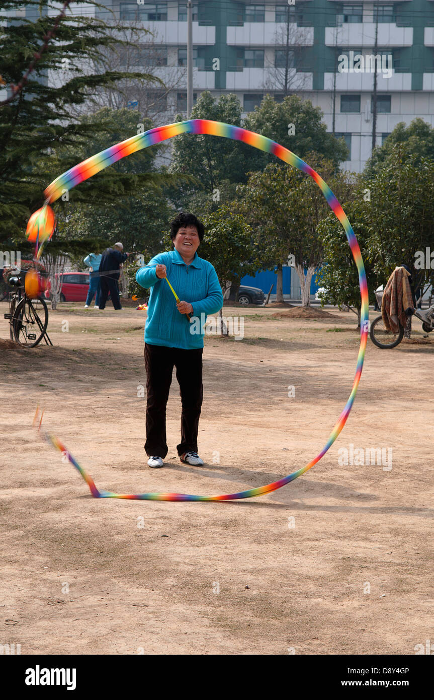 Woman in a blue sweater and sneekers relaxing in a municipal park spinning a top with a multicoloured tail with - Stock Image