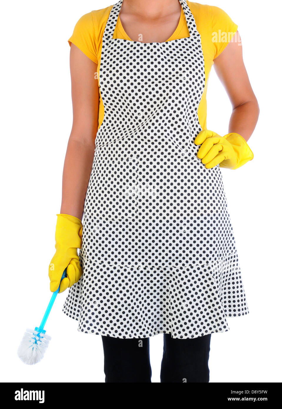 Closeup of a woman in an polka dot apron holding a toilet scrub brush. Woman has on yellow rubber gloves and is - Stock Image