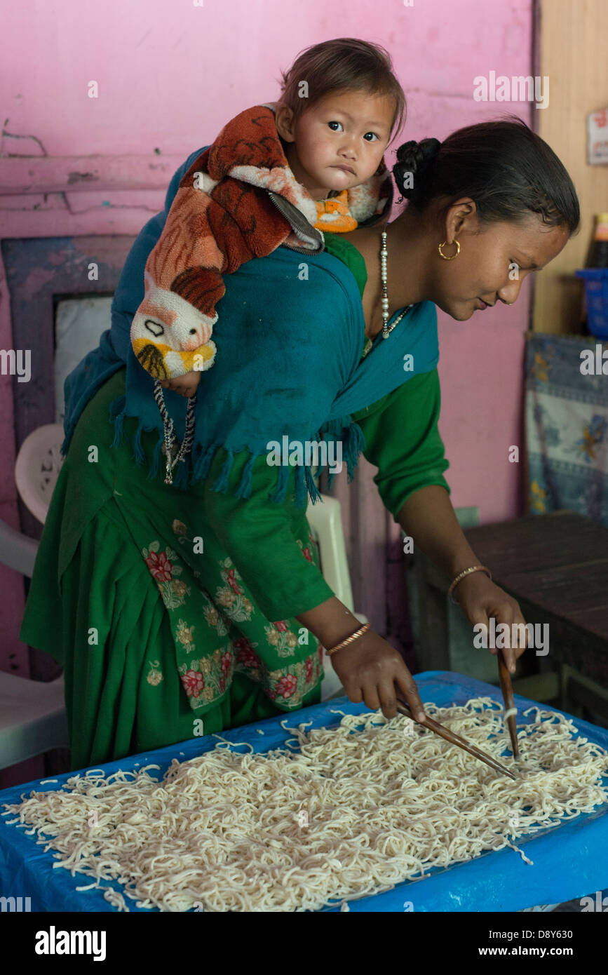 A migrant Nepalese mother prepares noodles at her restaurant in the Himalayan town of Bharmour, Himachal Pradesh, - Stock Image