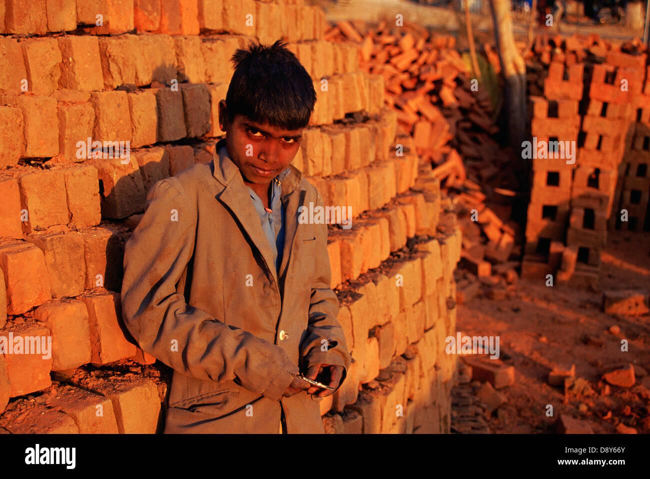 Boy working in a brickyard ( India) - Stock Image