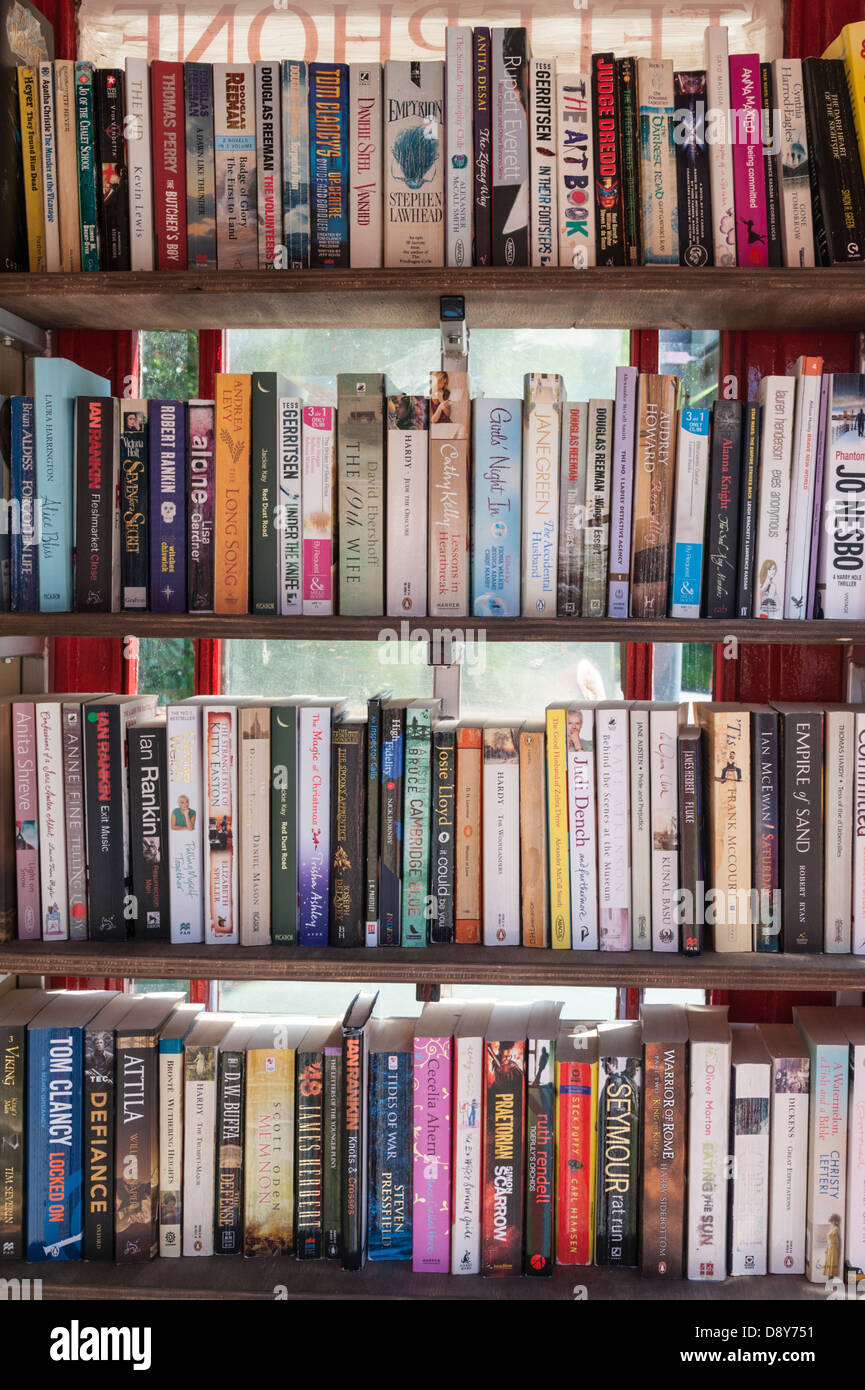 Secondhand books in a library in a disused telephone box in the village of Shepreth South Cambridgeshire UK - Stock Image