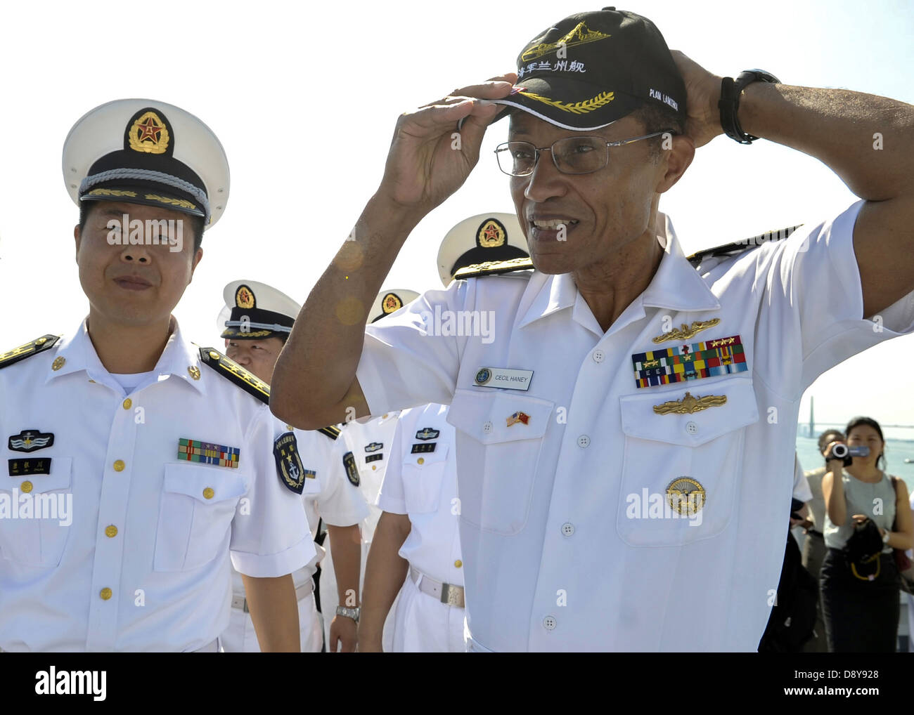 US Adm. Cecil Haney, commander of US Pacific Fleet, right, dons the baseball cap of the People's Liberation Army - Stock Image