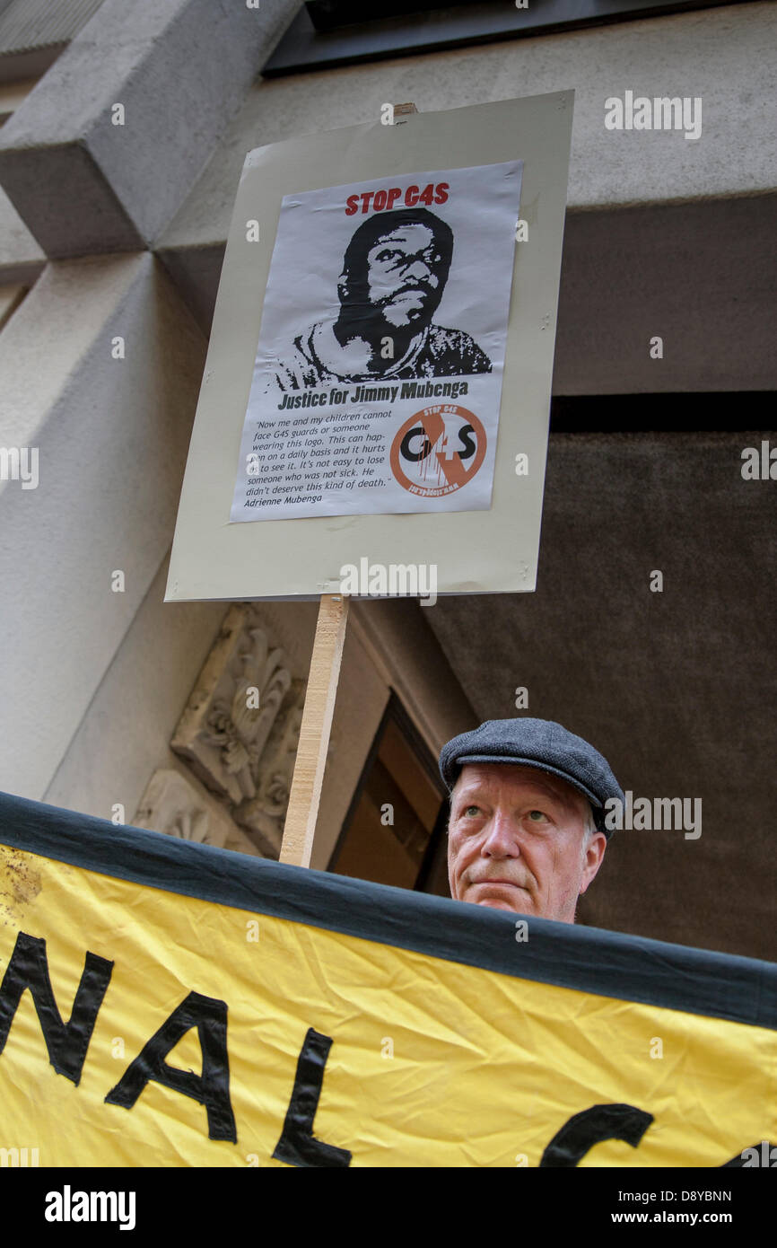 A protester outside the AGM of security multinational G4S demonstrates against the company who he accuses of being - Stock Image