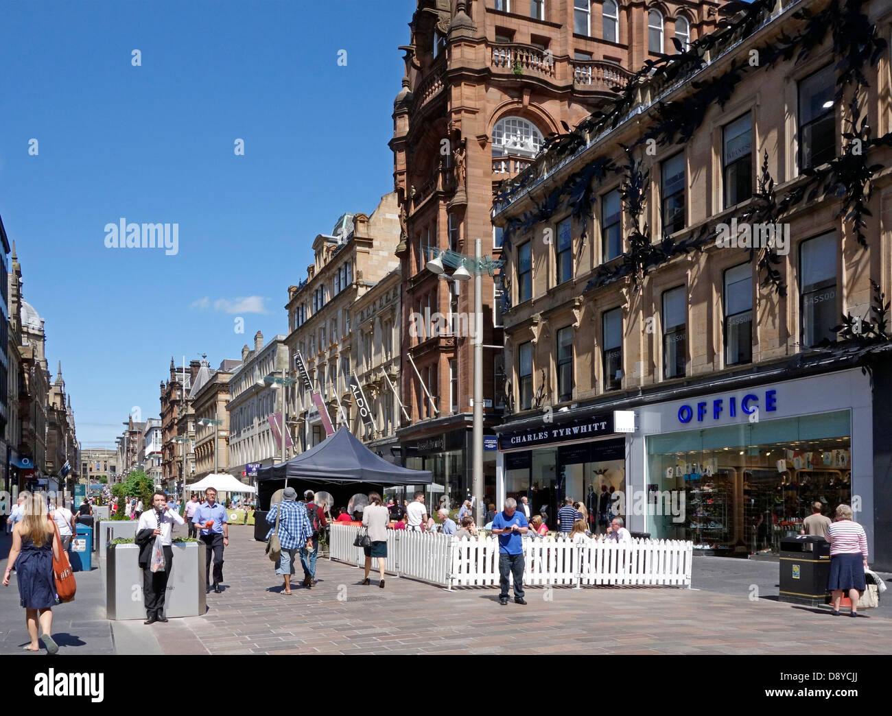 Buchanan Street in Glasgow Scotland on a busy day with shoppers and visitors enjoyind food and drink outside. - Stock Image
