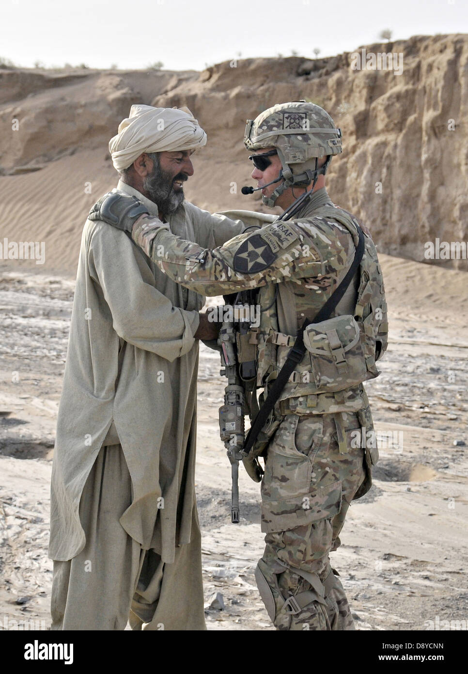 US Army Capt. Troy Yoho exchanges greetings with an Afghan farmer while his unit conducts a dismounted patrol June - Stock Image