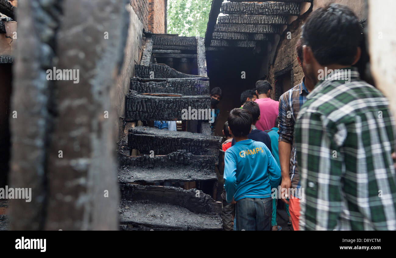 Ache Gous,Indian Administered Kashmir 6th June, 2013. Kashmiri Muslims look at a damaged residential house after - Stock Image