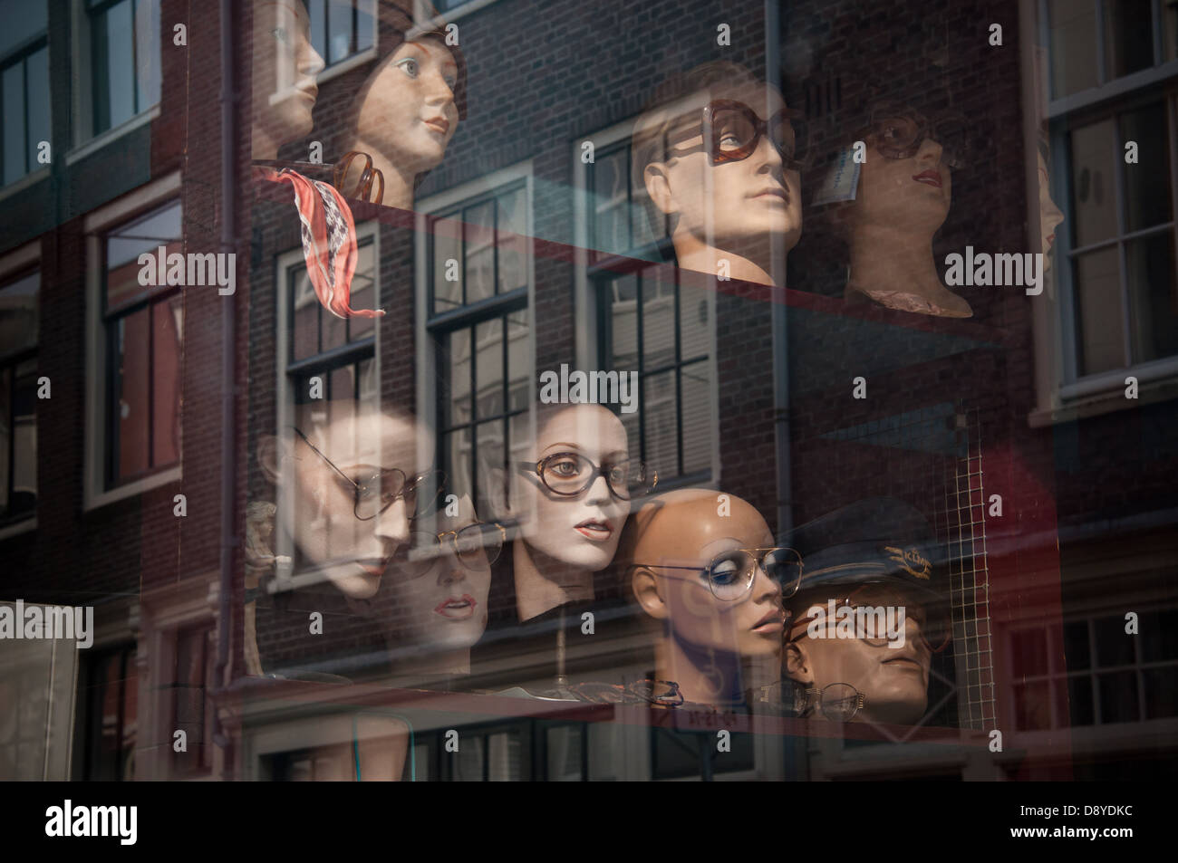 Mannequin heads on display in a junk shop window in Amsterdam. - Stock Image