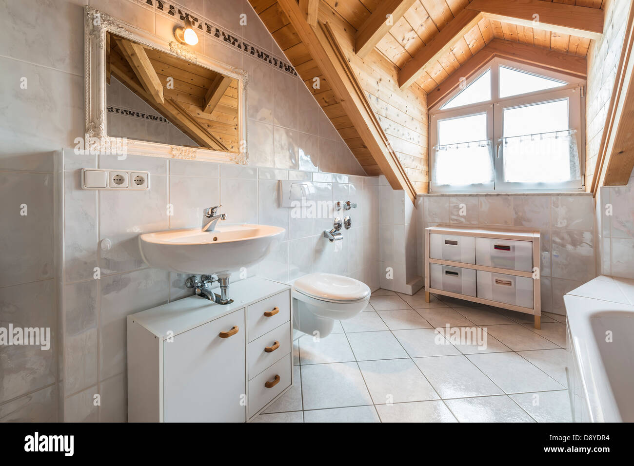 bathroom of a flat in attic with basin, mirror, light, window, toilet, bathtub, cabinets and wooden ceiling - Stock Image