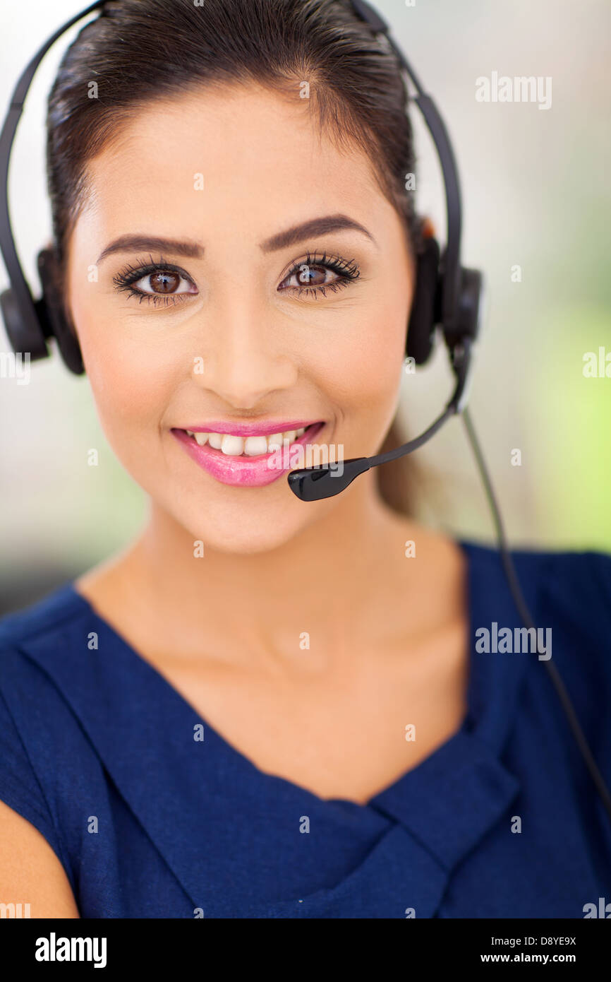 Closeup portrait of a happy young call center employee smiling with a headset Stock Photo