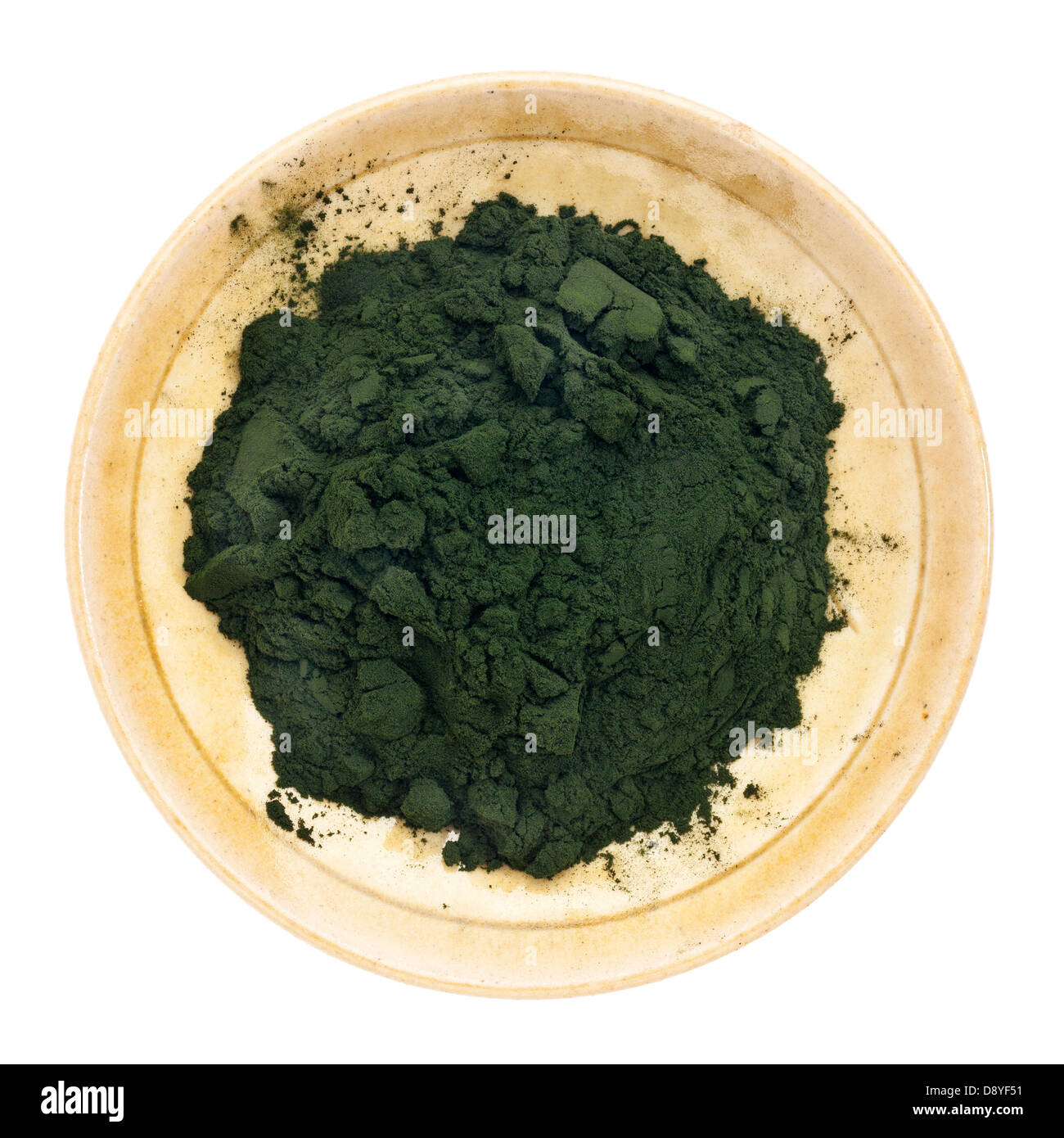 Nutrient-rich organic chlorella powder on a small ceramic bowl, isolated on white, top view - Stock Image