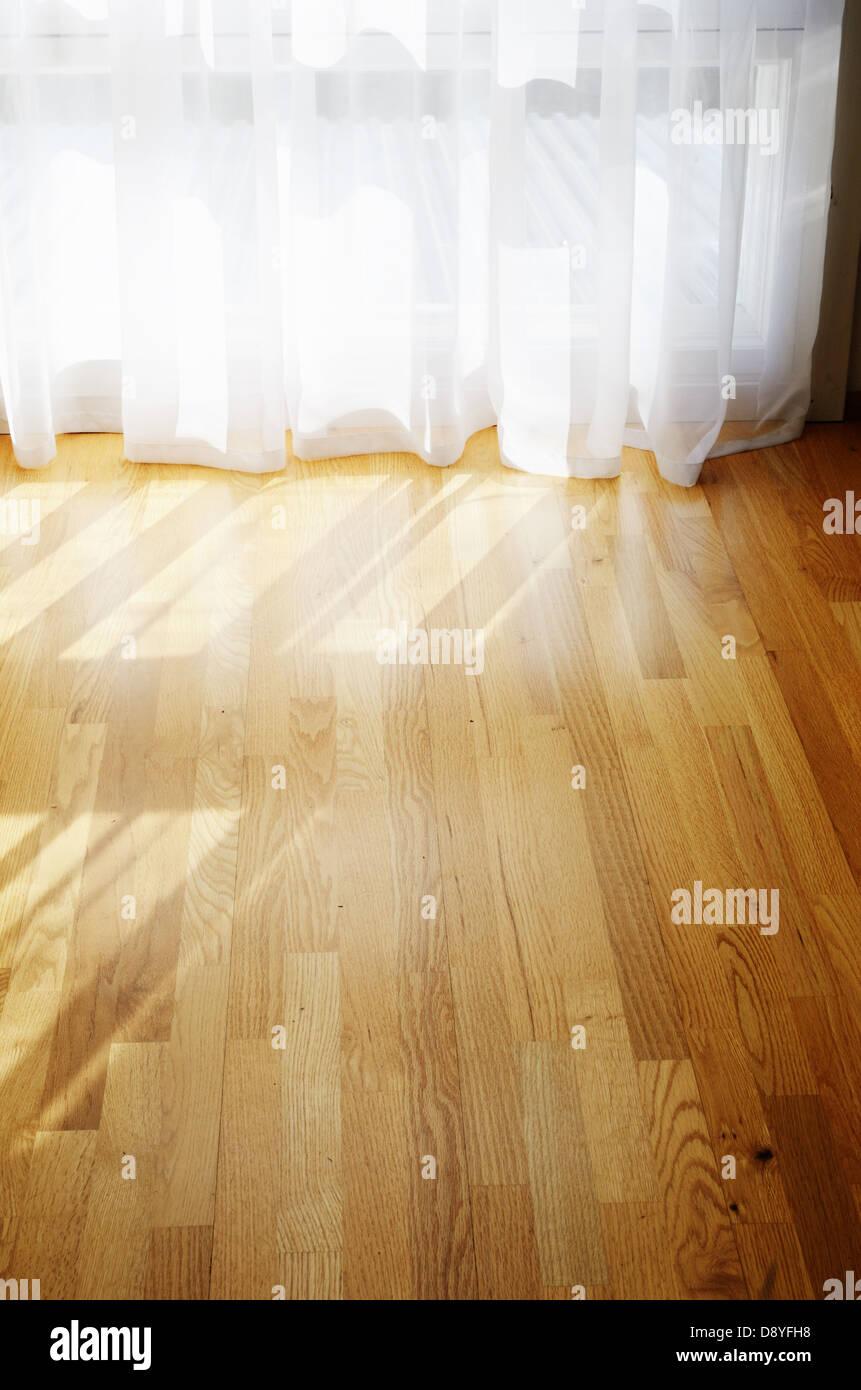 empty room, parquet flooring, transparent curtains - Stock Image