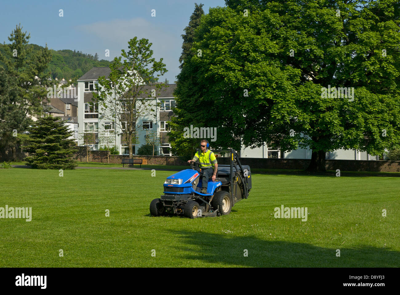 Council employee using ride-on mower to cut the grass in small park, Kendal, Cumbria, England UK - Stock Image